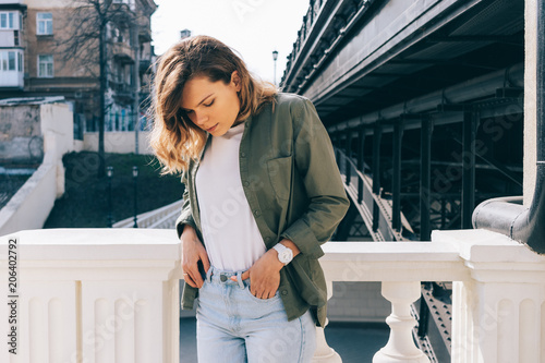 Fotomural Young woman with wavy hair standing next to a bridge