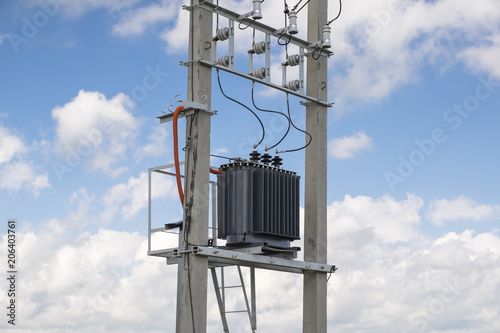 Photographie Electric transformer stands on concrete supports.