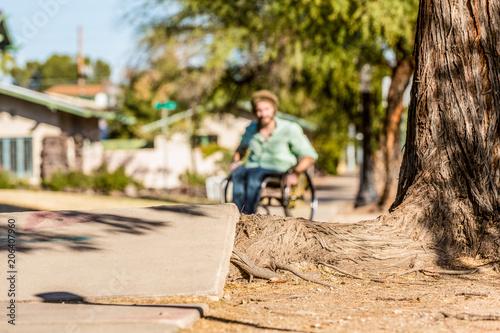 Fotomural  Deep Focus Man in Wheelchair Faces Sidewalk Obstacle