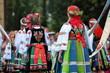 Dziewczyny ubrane w odświętne ludowe stroje łowickie idą w tradycyjnej procesji podczas święta Bożego Ciała, widok z tyłu, kolorowe stroje, słonecznie