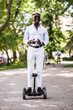 Young handsome afro american man driving on segway in the park