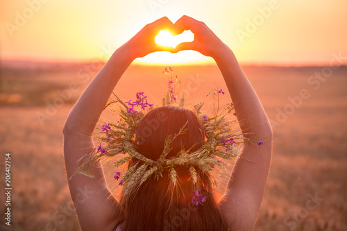 Poster Corail girl on wheat field making heart symbol at sunset