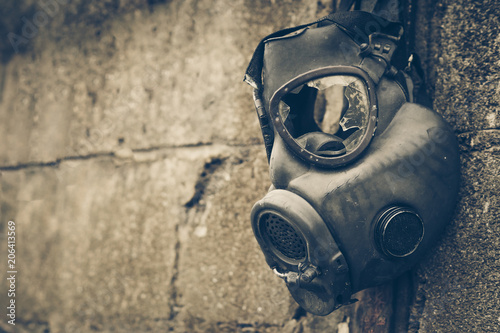 Photo  Broken gas mask hung on the wall / Toxic chemical weapon concept