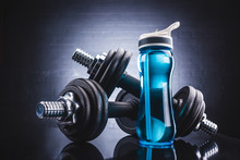 Close-up View Of Sports Bottle Full Of Water And Dumbbells, Sport And Healthy Lifestyle Concept