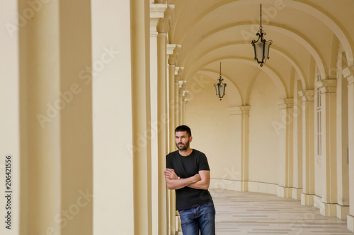 Valokuva Handsome young man standing outdoors under old colonnade