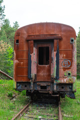 Fototapeta na wymiar abandoned burning car of a passenger train stands on the rails in the spruce forest on a Sunny day. tourist walk through the abandoned urban locations. equipment after disasters and military operation