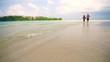Man and woman in bikini running on the beach