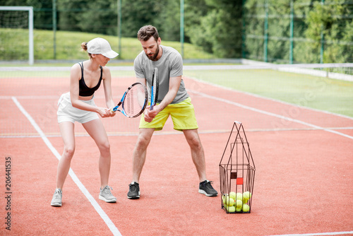 Fotografía  Male instructor teaching young woman to play tennis on the tennis court outdoors