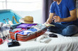 Travel and vacation concept, happiness young man packing a lot of his clothes and stuff into suitcase on bed prepare for travel and journey trip in holiday