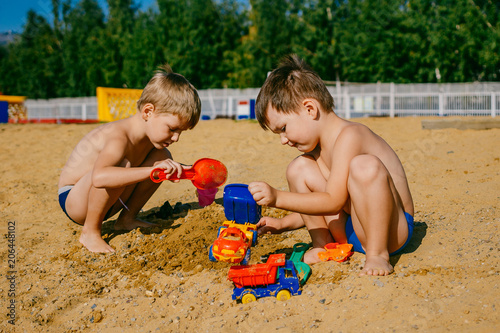 two little boys playing with cars on a sandy beach