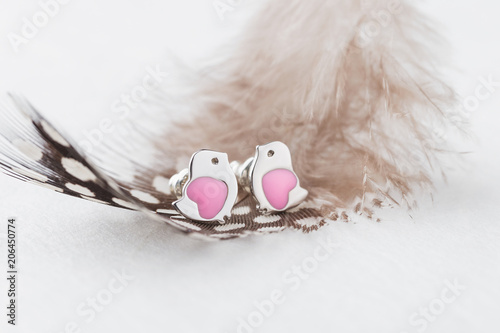 Bird shape with pink heart earring studs on white background with feather
