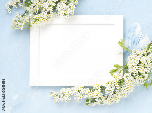 Tuinposter Bloemen White flowers over the frame on blue concrete background. Backdrop with copy space
