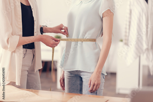 New dress. Close up of young professional tailor taking measurements of girls waist while being concentrated and precise
