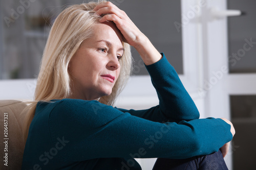 Leinwand Poster Sad depressed middle aged woman at home sitting on the couch, looking down and t