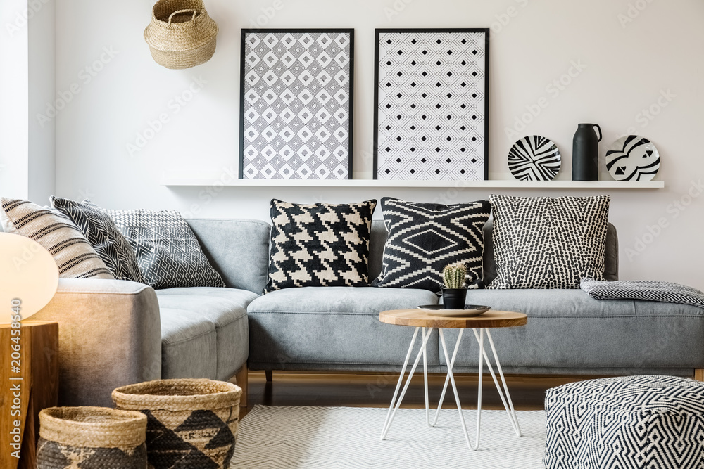 Fototapety, obrazy: Patterned pillows on grey corner sofa in apartment interior with posters and pouf. Real photo
