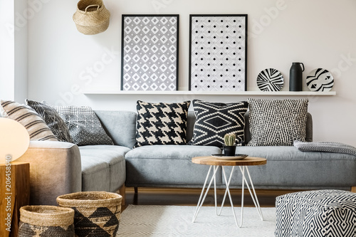 Patterned pillows on grey corner sofa in apartment interior with posters and pouf. Real photo