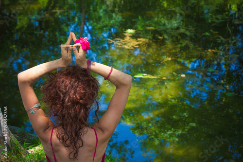 woman practice yoga meditation in front lake hands in mudra gesture with flower Wallpaper Mural