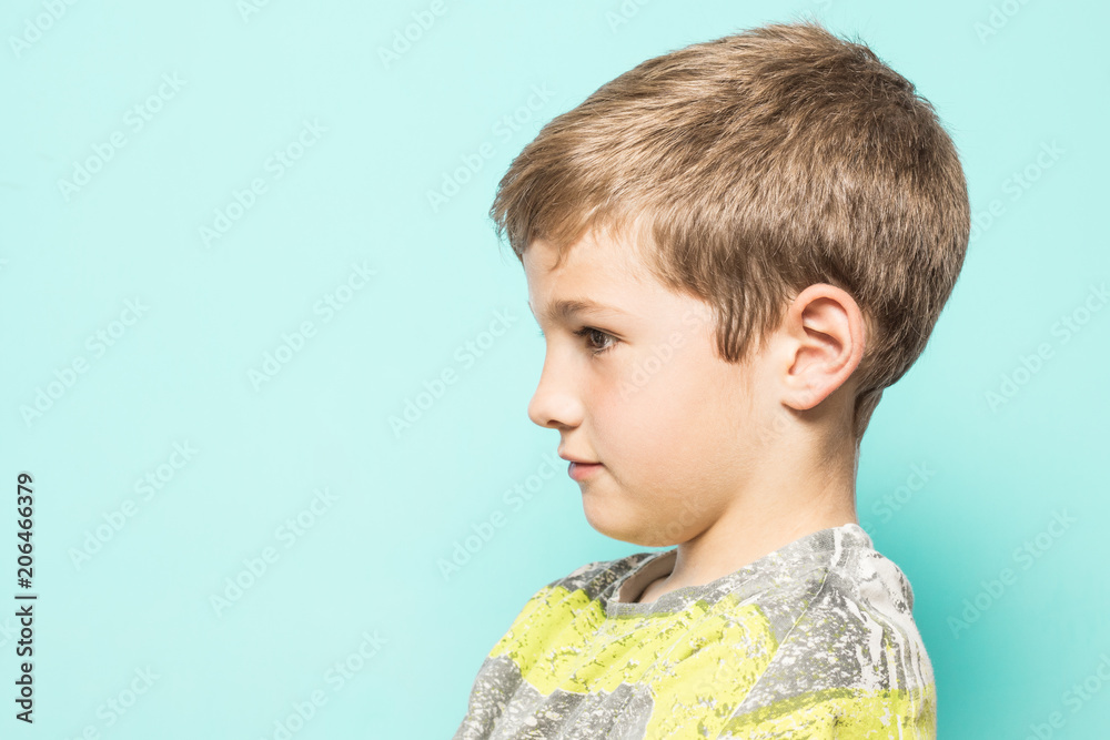 Fototapeta Serious child in profile on a blue background