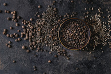 Variety Of Different Black Peppers Allspice, Pimento, Monks Pepper, Peppercorns And Ground Powder In Tin Can Over Old Black Iron Texture Background. Top View, Space.