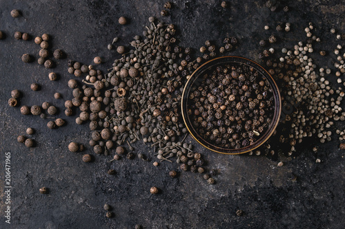Papel de parede Variety of different black peppers allspice, pimento, monks pepper, peppercorns and ground powder in tin can over old black iron texture background