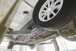 Car on a wheel alignment lift in auto service. Diagnosis of the chassis of the car raised at the elevator. toning