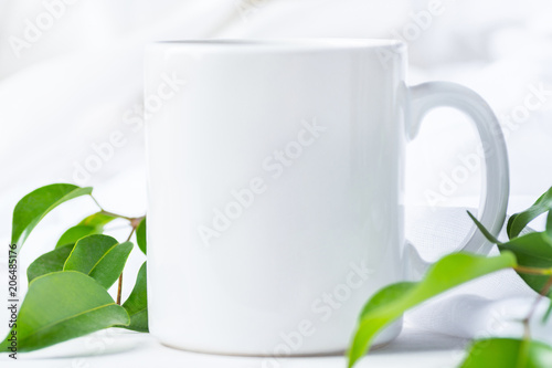Blank White Mug Mockup on Cotton Linen Fabric Background. Fresh Tree Branches with Green Leaves. Template Space for Creative Artwork Lettering Text Product Promotion Branding. Elegant Feminine Style