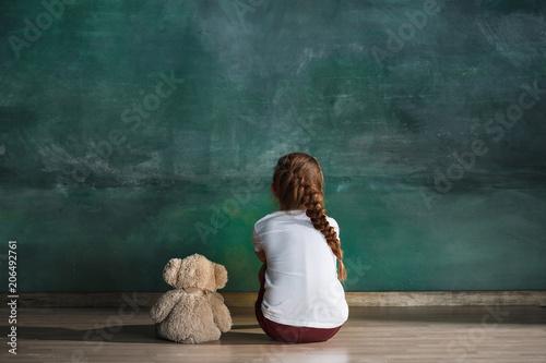 Fototapeta Little girl with teddy bear sitting on floor in empty room. Autism concept obraz na płótnie
