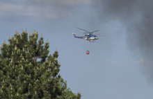 Fire Rescue Police Helikopter Delivering Water Bucket For Aerial Firefighting, Smoke And Blurred Pine Tree, Blue Sky Byckground