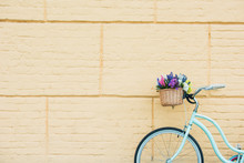 White Bicycle With Beautiful Flowers In Basket Near Wall