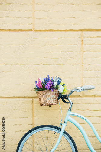 Foto op Plexiglas close-up view of bicycle with beautiful colorful flowers in basket near wall