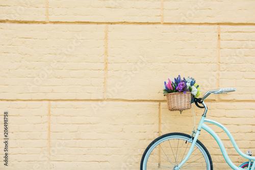 Foto op Plexiglas white bicycle with beautiful flowers in basket near wall