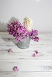 Flowers of lilac.White old background with space for text.Purple color.lilac in a small bucket