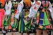 Młode dziewczyny ubrane w ludowe tradycyjne stroje łowickie, idą w grupie, uroczyśćie,  jedna za drugą, prezentująć kolorowe wyszywane stroje