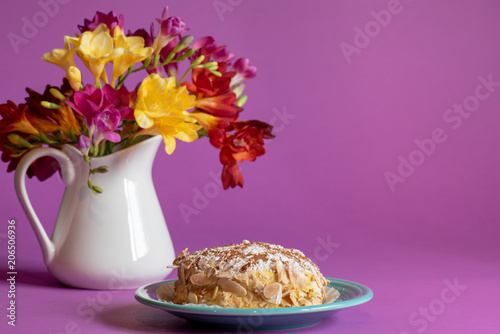 Fotografie, Obraz  Portuguese pastry on a turquoise plate with a pitcher of freesia flowers behind it on a purple background