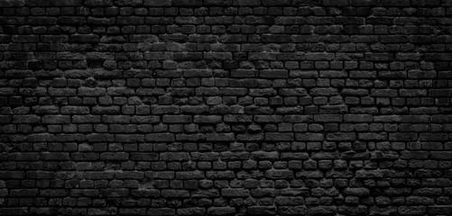 Old black brick wall panorama background.