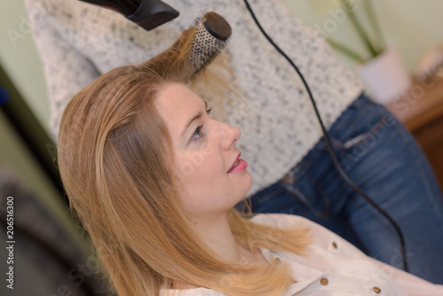 hairdresser drying clients hair and using round brush