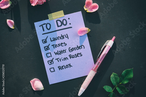 Photo  To do list on purple paper with pen and rose petals.