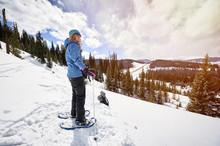 A Young Woman Snowshoeing On T...