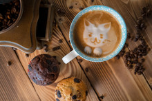 Cat Foam Face Of Latte Art Coffee In Cup With Scattered Coffee Beans And Biscuits On Old Wooden Table