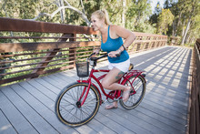 Young Blond Female Riding A Beach Cruiser Bike Over A Bridge