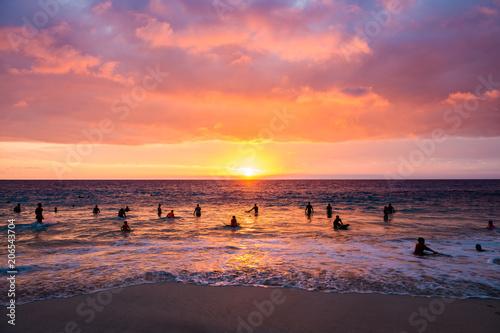 夕暮れの海で遊ぶ人々のシルエット