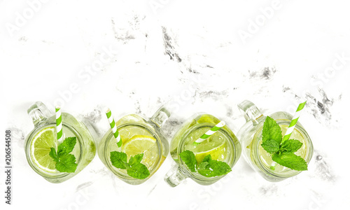 Obraz na plátně  Cocktail drink lime lemon mint ice summer lemonade Top view