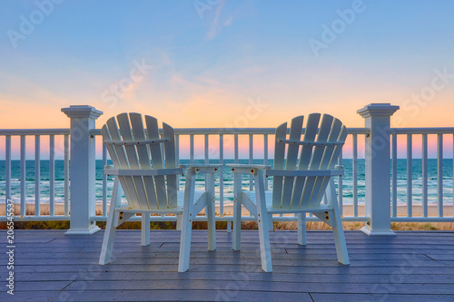 Photo Adirondack Chair sits on the balcony deck of a house looking out over the beach