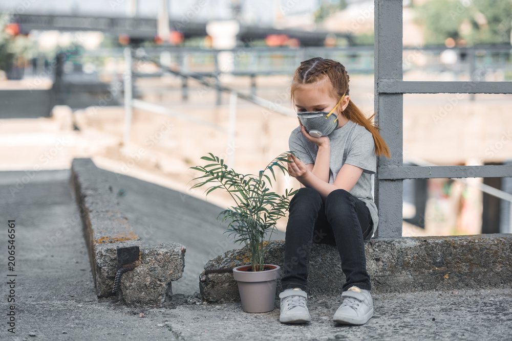 Fototapeta child in protective mask looking at green potted plant, air pollution concept