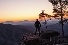 A Man Stands On The Edge Of A Rock