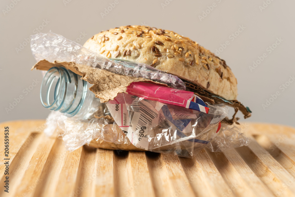 Fototapeta Fresh tasty burger with plastic waste and paper cardboard inside on wooden board. Recycled waste in our food concept