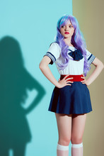 Young Beautiful Woman In Bright Wig And Skirt Standing With Hands On Waist And Looking Away In Studio