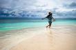 happy girl runs barefoot along the ocean shore