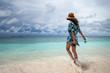 Happy girl running along the ocean shore