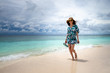 Happy girl walking along the ocean shore
